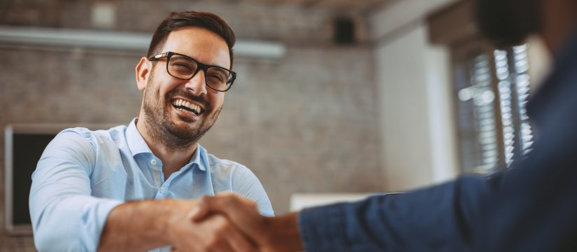 Employee with straight, white teeth shakes hand with happy boss